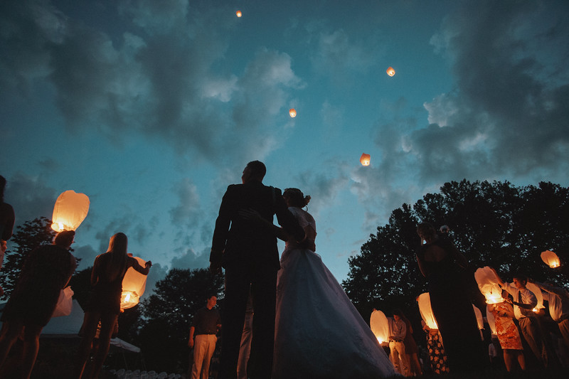 The bride and groom watch as their guests release their lanterns into the sky.