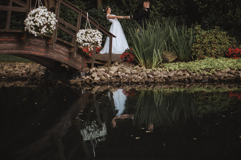 The bride and groom pull each other in opposite directions as they're reflected in a garden pond.