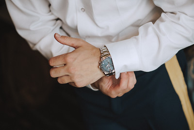 Groom putting his watch on.
