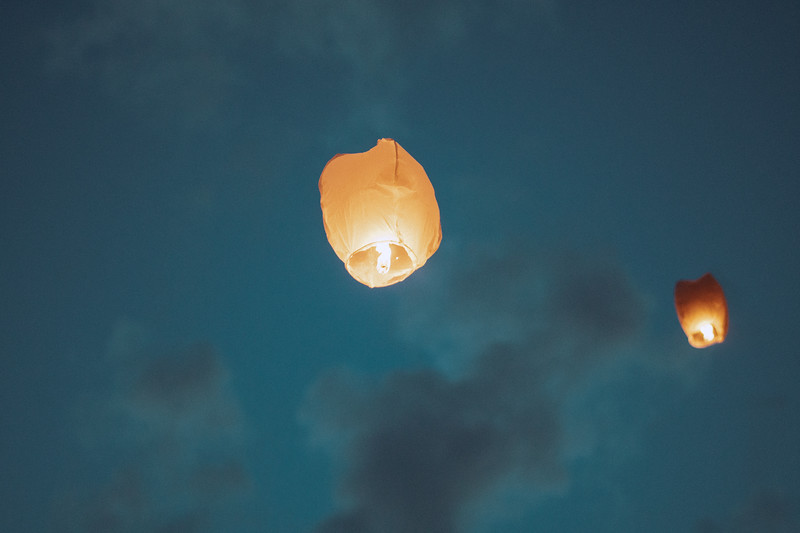Chinese lanterns float away into the pale blue evening sky.