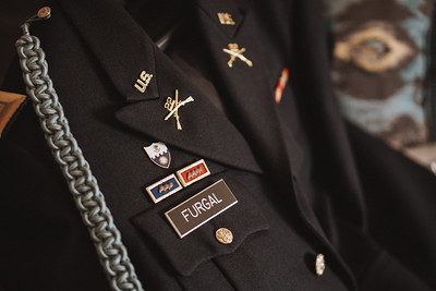 Groom's Army officer dress jacket with pins and awards.