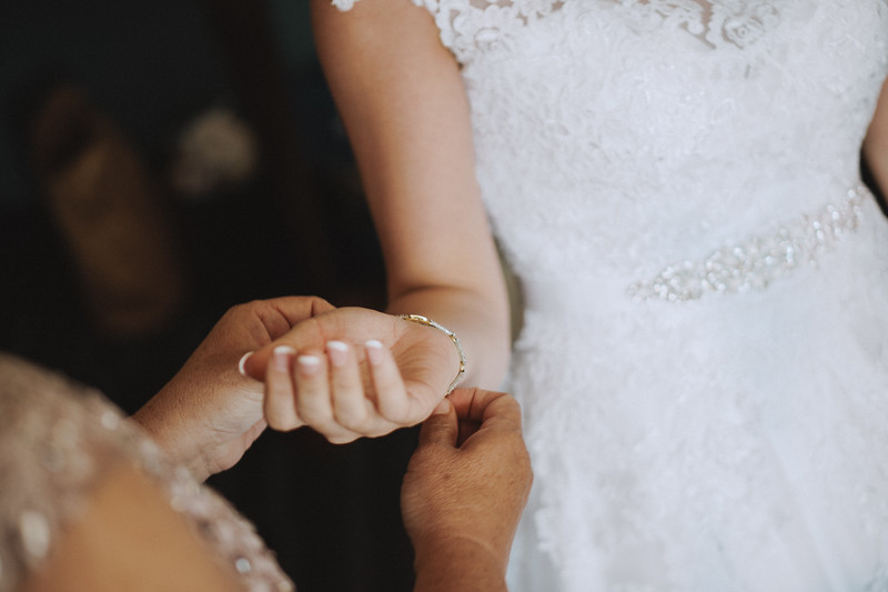 Bride's mother placing a bracelet on her wrist.