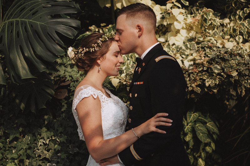 Against a lush, tropical backdrop, the groom gently kisses the brides's forehead as she smiles.