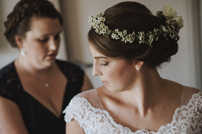 Bride looking over her shoulder as her sister buttons up her wedding gown.