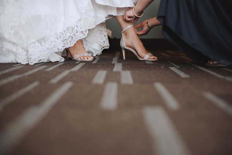 Bride's sister helping her close the strap on her heels.