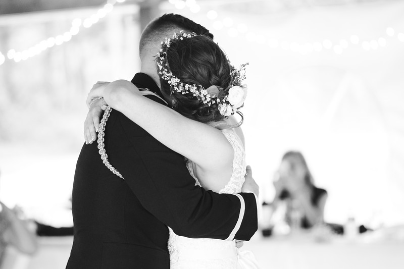 The bride and groom embrace as they slow dance.