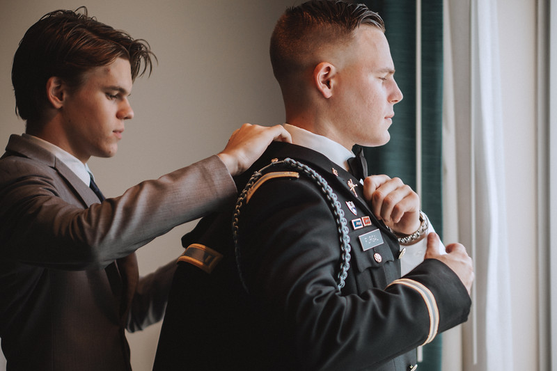 Groomsman helps the groom into his jacket.