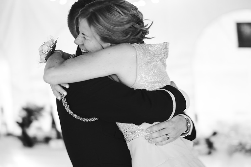 The groom's mother laughs as he hugs her tightly and picks her up.