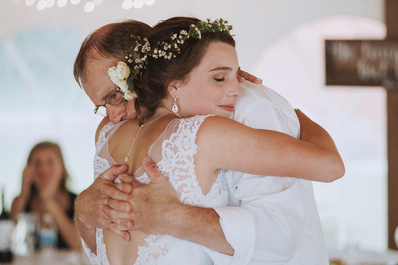 The bride and her father smile warmly while embracing.