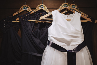 Bridesmaid's and flower girl dresses hanging on hand painted hangers.