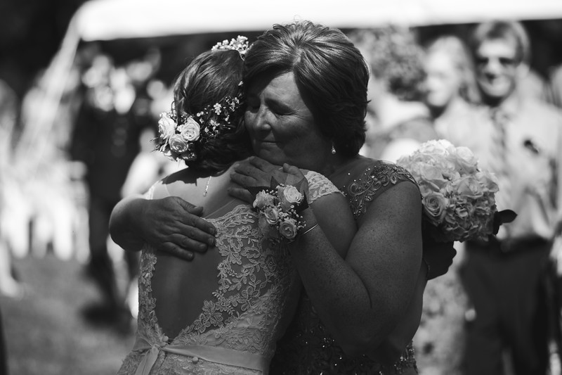 The bride's mother, overcome with joy, hugs her gently.
