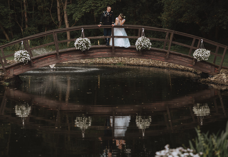 The bride and groom on a bridge look into one another's eyes as they're reflected in the pond below.