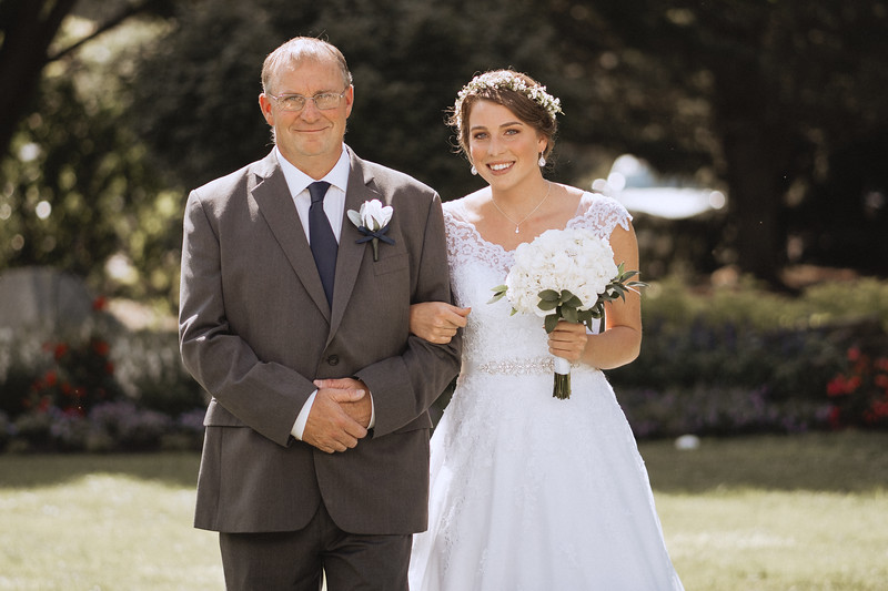Bride smiles as she walks down the isle with her father.
