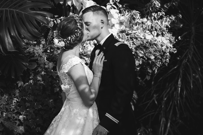 The bride and groom kiss in the greenhouse against a backdrop of plants.