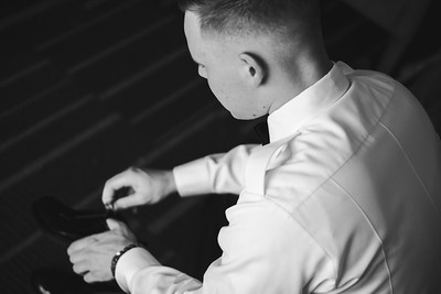Groom putting his shoes on.