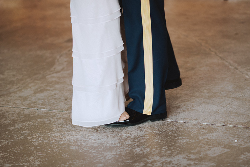 The groom's mother stands on his feet as they slow dance.