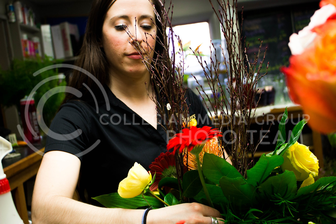 Kristner's Flowers' employee plants a red flower in a boque on Feb.13. <br /> (Alanud Alanazi | The Collegian)