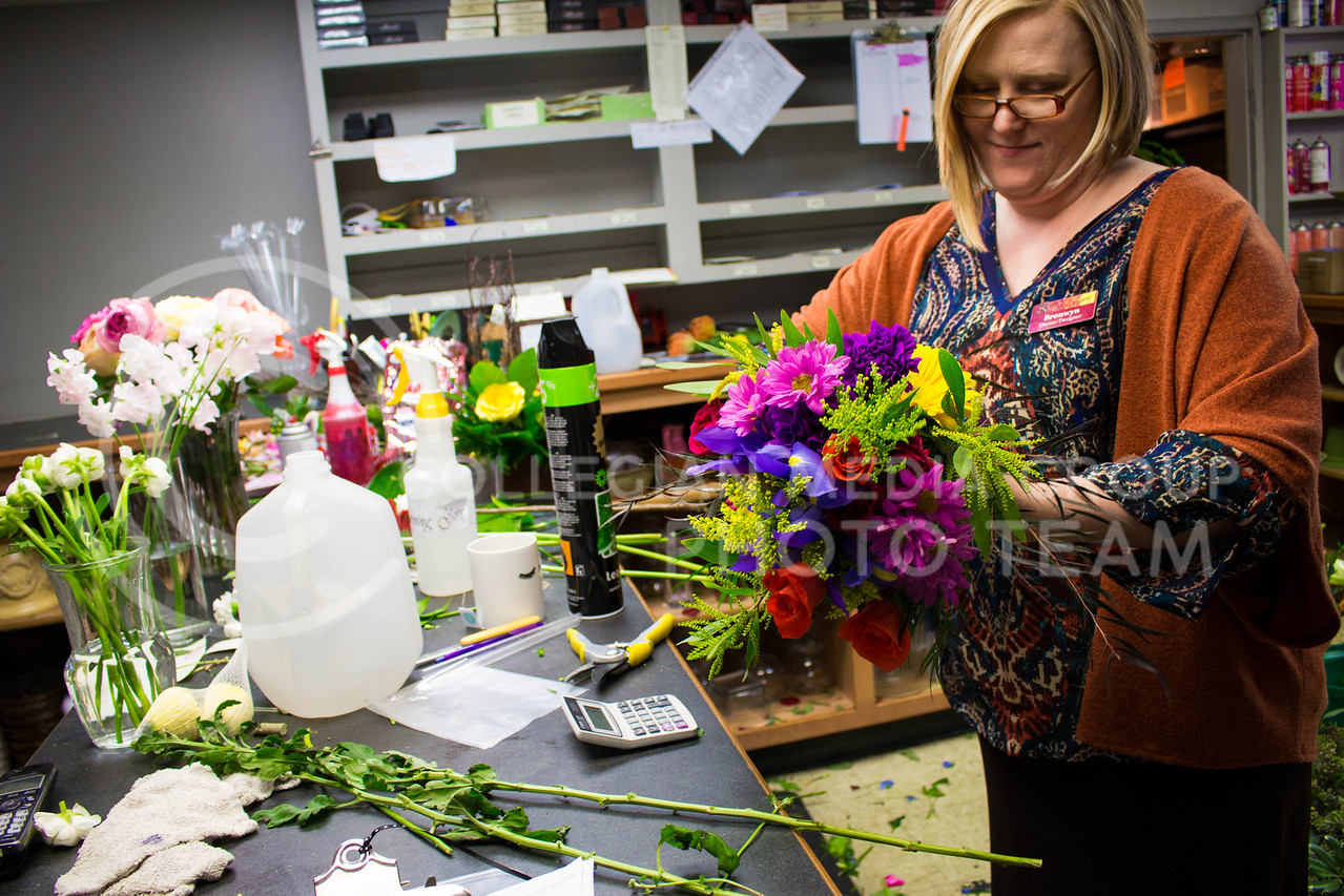 Bronwyn Douglas, owner and designer at Kristner's Flowers, finshes up arranging flowers for a customer on Feb.15. <br /> (Alanud Alanazi | The Collegian)