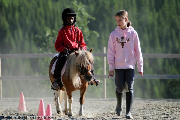 Anisha (8) lærer å ri på Gunn Kaianders rideskole i Håkvik. Camilla (10) er dyktig lærer. Tålmodig hest er Lotta. Juli 2008.