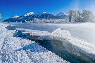 Snowy Swiss winter landscape with frozen river Inn and beautiful ice crystal formations on a sunny day