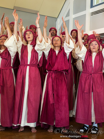 Prophets of Baal dressed in red raise their arms to their god.