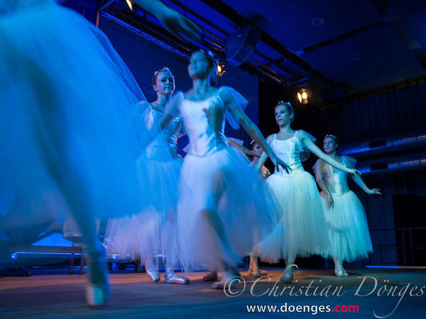 Dancing ballerinas in white tulle glide on stage as angels.