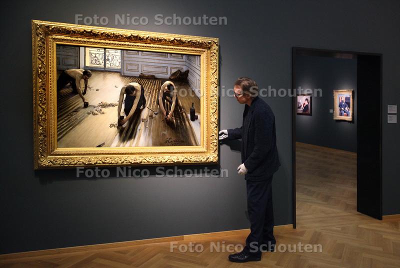 """Expositie van Gustave Caillebotte, een Franse impressionist in het Gemeente Museum. Conservator Franz Kaiser zet de stipjes op i bij de """"De Paerketachavers"""" uit 1875 - DEN HAAG 1 FEBRUARI 2013 - FOTO NICO SCHOUTEN"""
