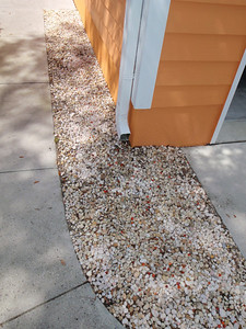 Orange glass stones added to rock bed at side of house