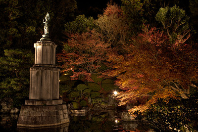 Buddhist Statue located in a pond with Autumn Foliage  At Chion-in Monastery, Kyoto, at Night