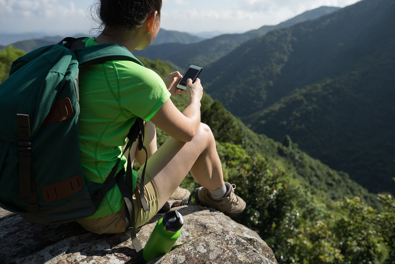 Hiker with smartphone. Editorial credit: lzf / Shutterstock.com