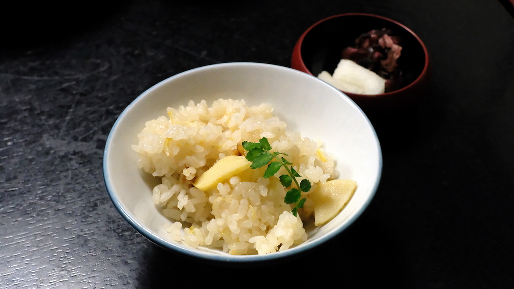 Rice cooked with bamboo shoots, served with pickles.