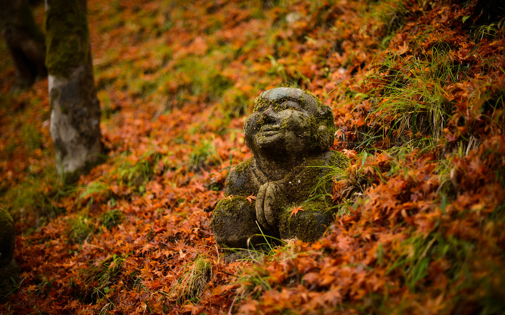 Jizo figure praying in the leaves  : copyright Jeffrey Friedl