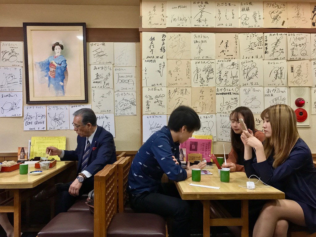 The wall of Okaru is papered with celebrity autographs