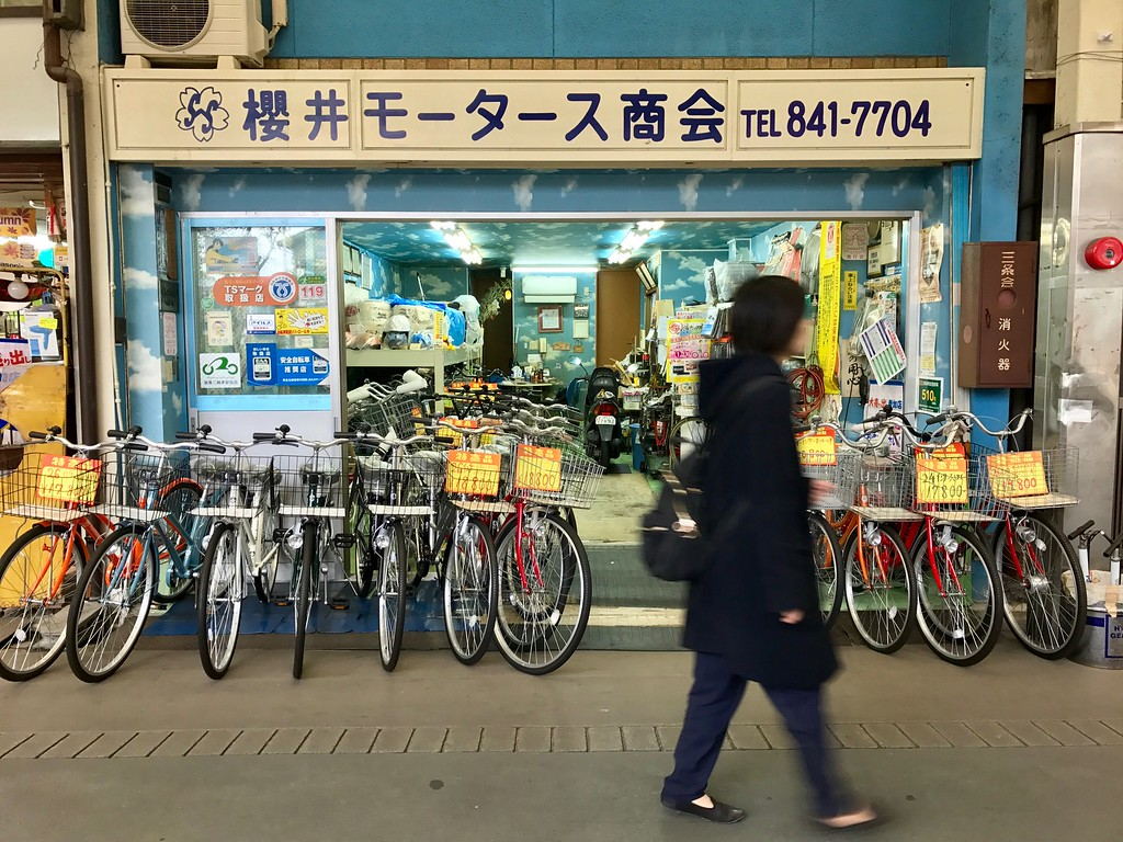A passerby in front of bicycle shop, Sakurai Motors.
