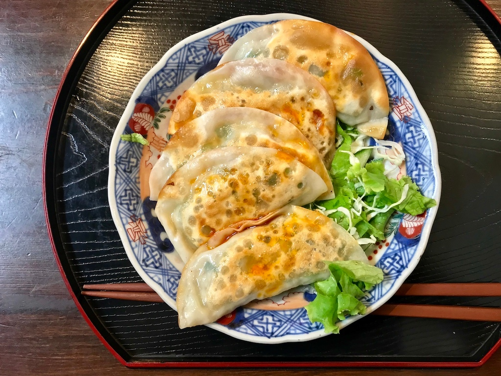 A plate of vegetable gyoza drizzled with vinegar and chilli oil.