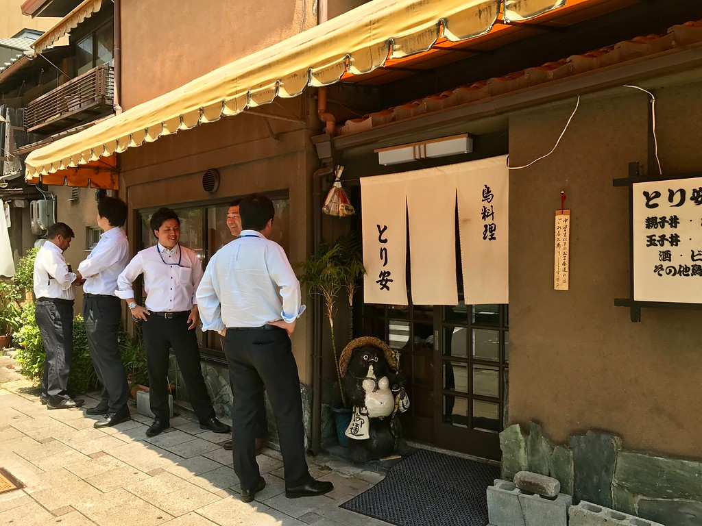 A queue of salarymen outside Toriyasu on a hot day.
