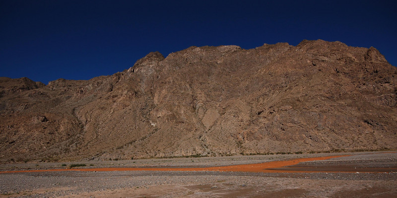 China, Torugart pass: Minerals colour the river orange, on the way to the Torugart pass.