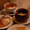A hearty Russian feast: crepes with cream, pelmeni in a pot, and borscht.