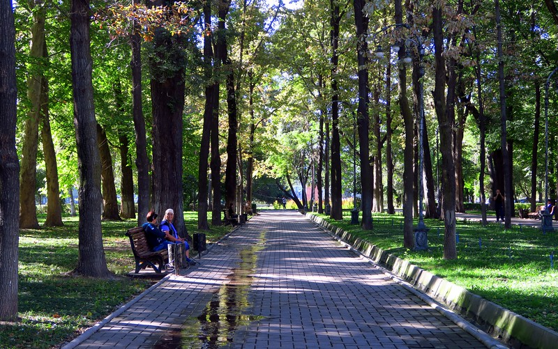 People sitting down on a park bench at Erkindik Park in Bishkek, Kyrgyzstan