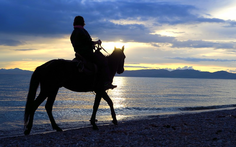 Horse riding along Song Kol Lake in Kyrgyzstan