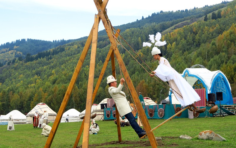 One of the traditional Kyrgyz swings with two people standing up going back and forth at the World Nomad Games