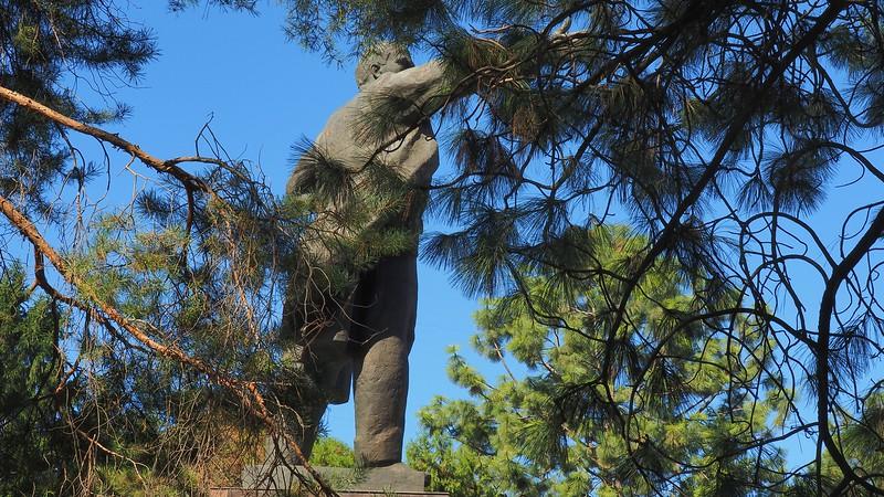 Lenin statue monument as viewed through tree branches in Bishkek, Kyrgyzstan