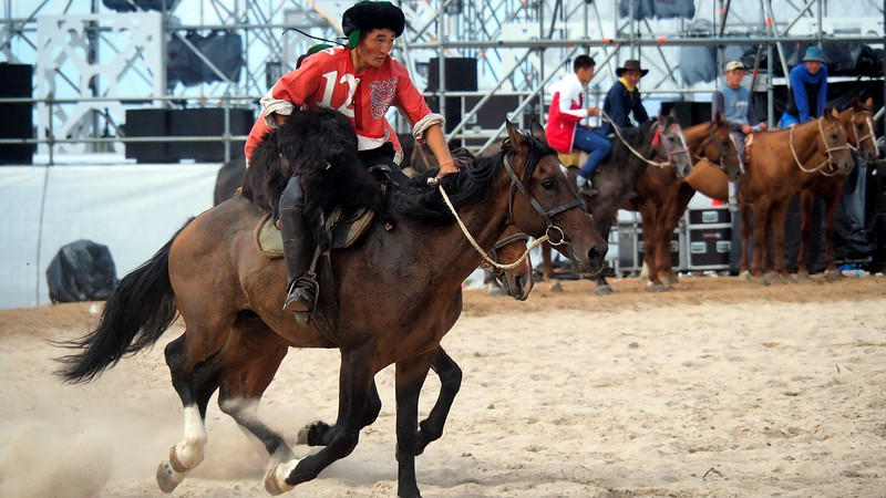 A Kok Boru player from Team China carries the goat carcass during a match at the World Nomad Games against the United States of America