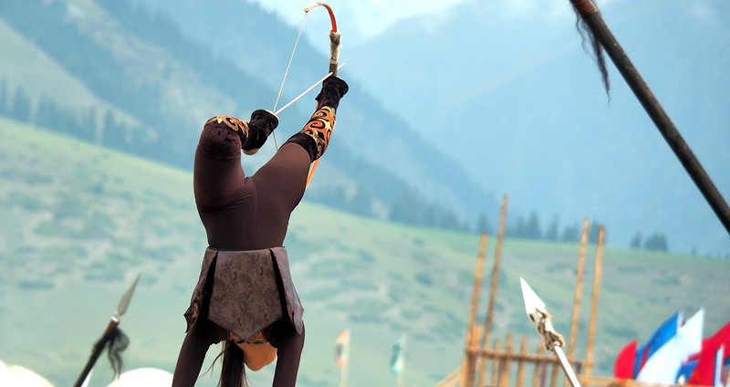 A lady shooting a bow and arrow while standing upside down during the World Nomad Games in Krygyzstan