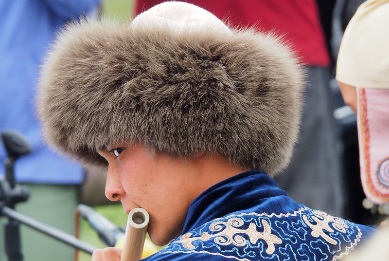 A close-up shot of a man wearing a traditional hat performing traditional Kyrgyz music at the event