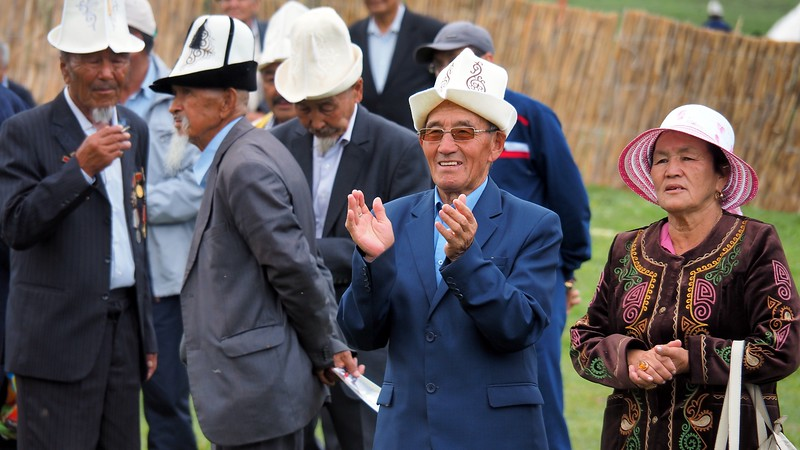 A Kyrgyz man wearing a traditional hat clapping during a musical performance at the World Nomad Games in Krygyzstan