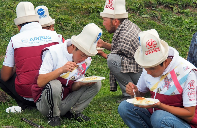 Kyrgyz men squatting down to enjoy a plate of Plov during the Kyrgyzstan World Nomad Games