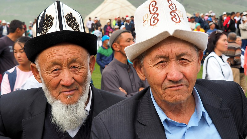 Two Kyrgyz men with distinct faces at the nomad games in Kyrgyzstan