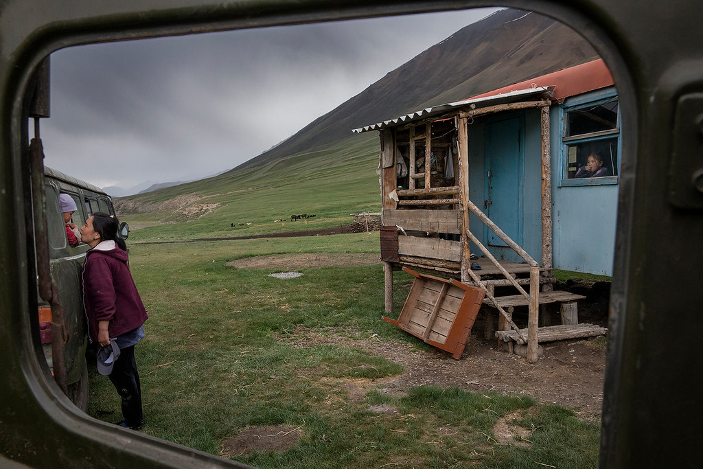 Semi nomad camp. A mother kisses her child while the sister looks at them from window of their small hut.