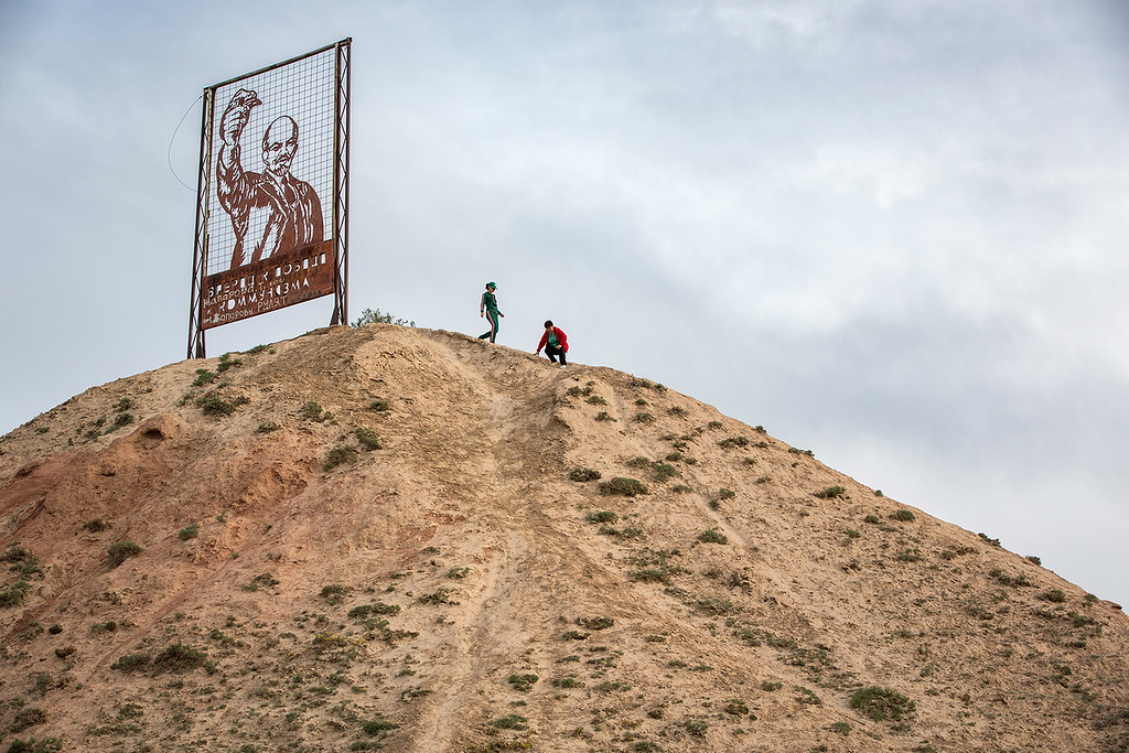 Women climbing a top where a big picture of Lenin is made from steel.
